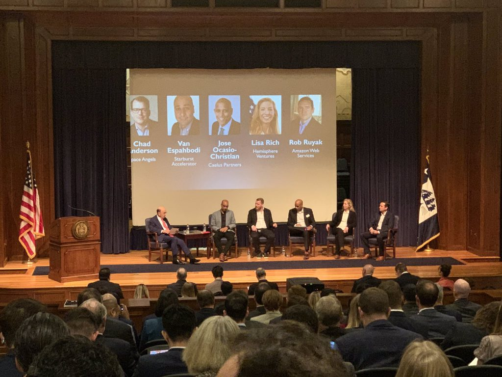 Secretary Ross seated on stage with five panelists in front of large audience