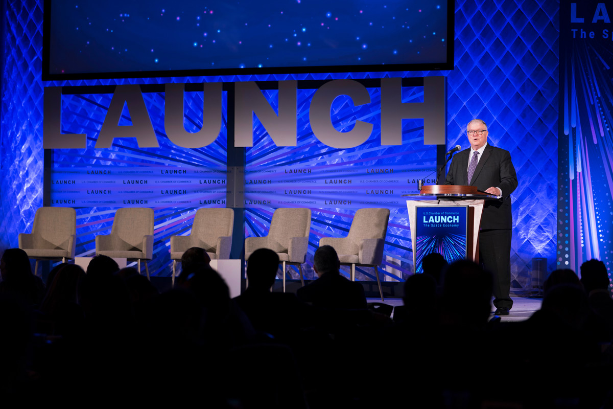 "Kevin O'Connell at podium with ""LAUNCH"" event backdrop"