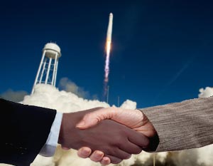 Business handshake with rocket launching in background